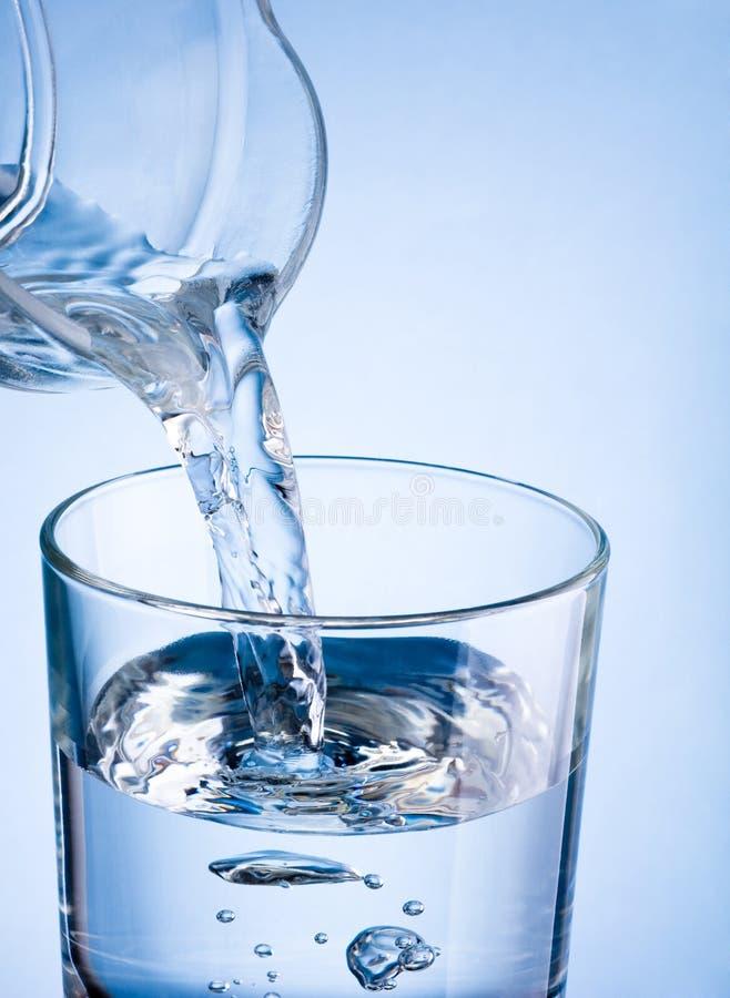 Hällande vatten för närbild från en tillbringare in i exponeringsglas på en blå backgroun royaltyfria foton