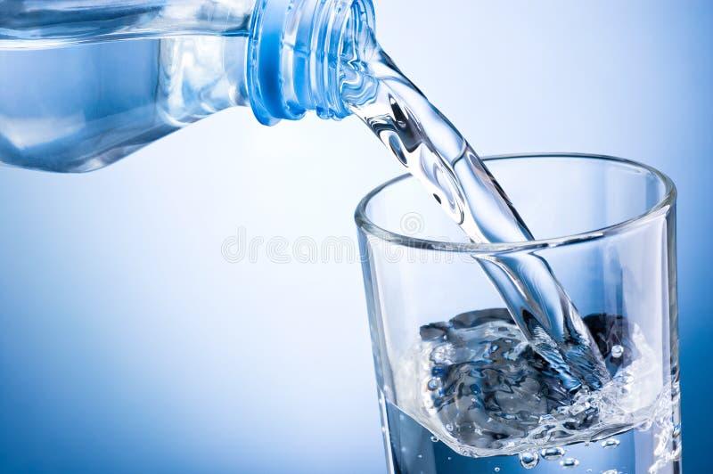 Hällande vatten för närbild från flaskan in i exponeringsglas på blå backgrou arkivfoton