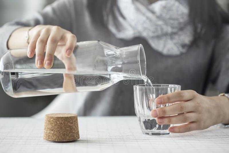 Hällande vatten för ung kvinna från flaskan till exponeringsglas royaltyfri bild
