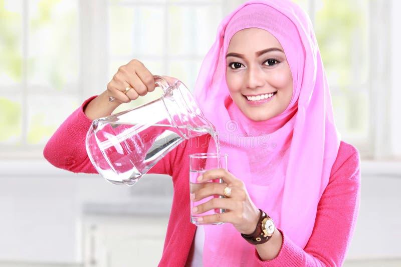 Hällande vatten för ung muslimkvinna in i ett exponeringsglas fotografering för bildbyråer
