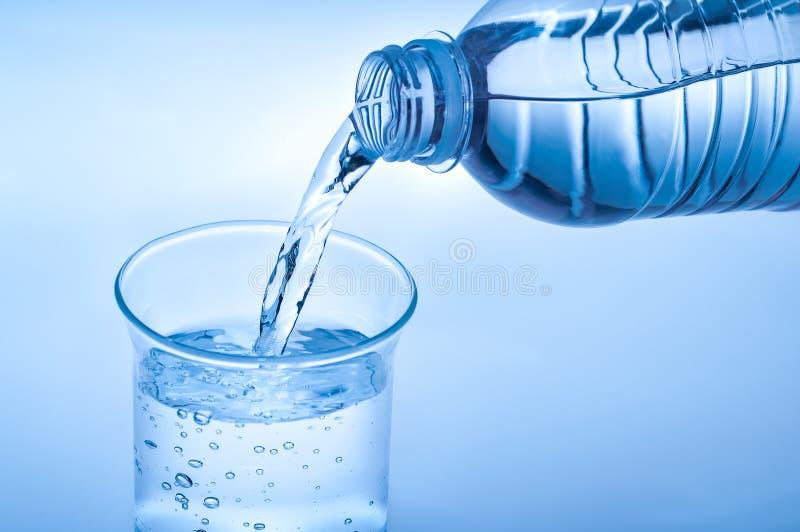 Hällande vatten från flaskan in till exponeringsglas på ljust - blå bakgrund arkivfoton