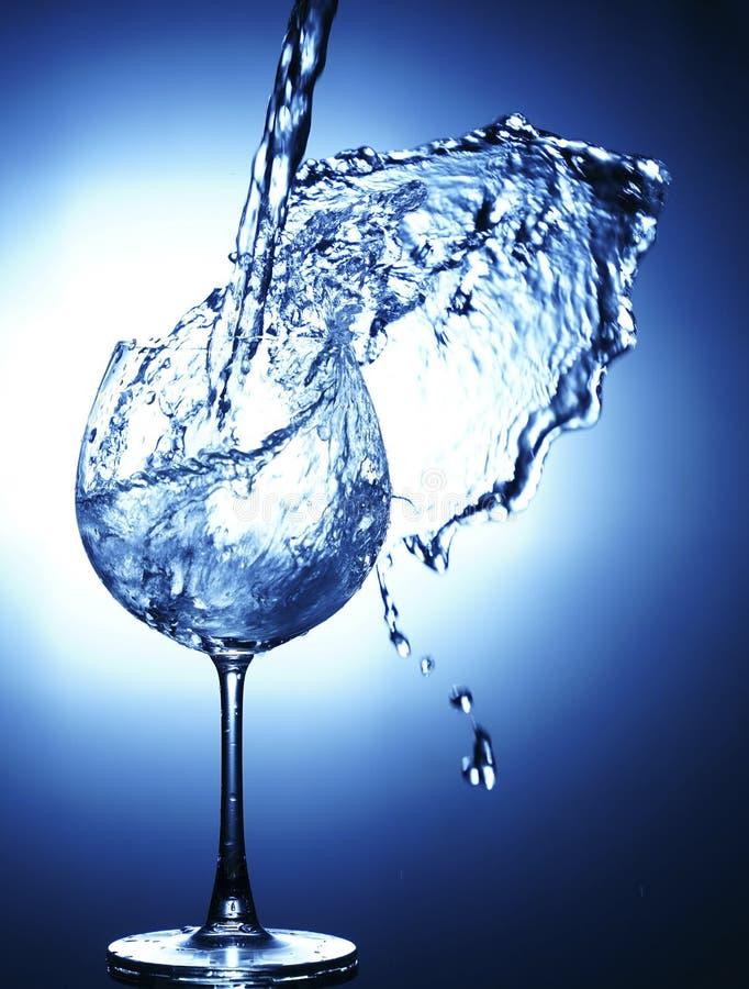 Hällande vatten in i exponeringsglas med plaskat ut fotografering för bildbyråer