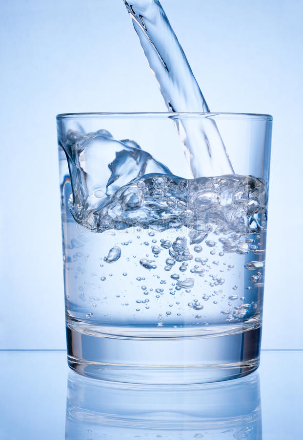 Hällande vatten in i exponeringsglas på blå bakgrund royaltyfri fotografi