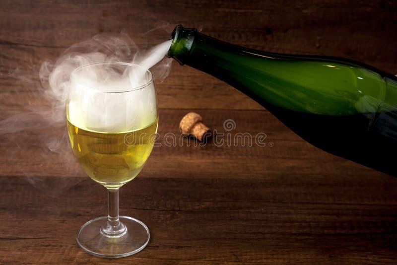 Hällande vin eller champagne från den gröna flaskan in i vinexponeringsglaset med någon rök på träbakgrund, för beröm eller parti royaltyfri fotografi
