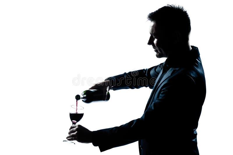 Hällande vin för manstående i ett exponeringsglas arkivbilder