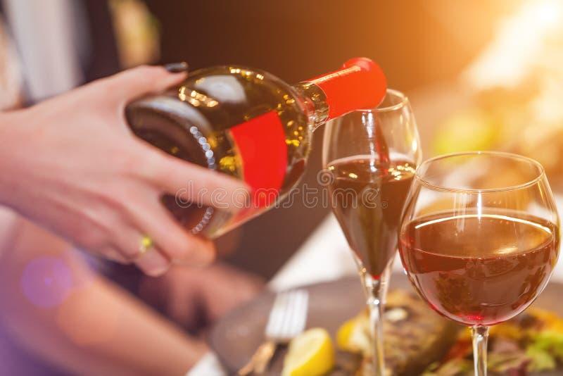 Hällande vin för uppassare in i exponeringsglaset i restaurang arkivbilder