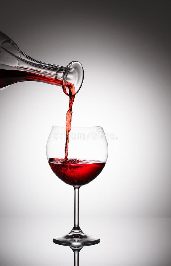 Hällande vin från en flaska in i ett exponeringsglas royaltyfri bild