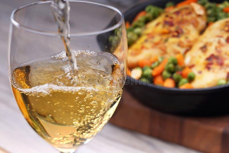 Hällande vitt vin och mat royaltyfria foton