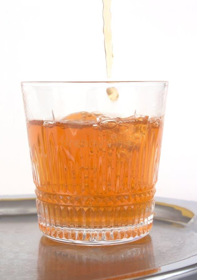 Hällande whiskey till exponeringsglaset royaltyfri bild