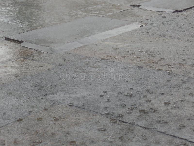 Hällregn som faller på trottoaren royaltyfria bilder