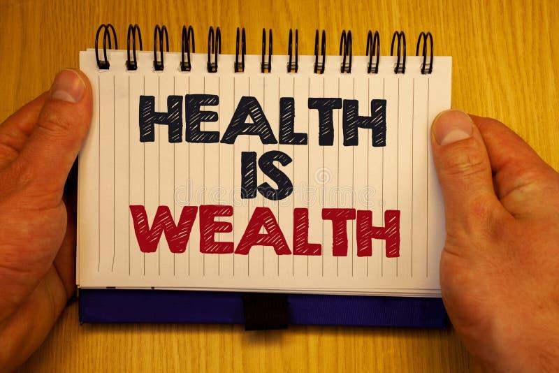 Hälsa för ordhandstiltext är rikedom Affärsidéen för att vara i det sunda staget för stort värde för bra form äter sunda legitima arkivfoto