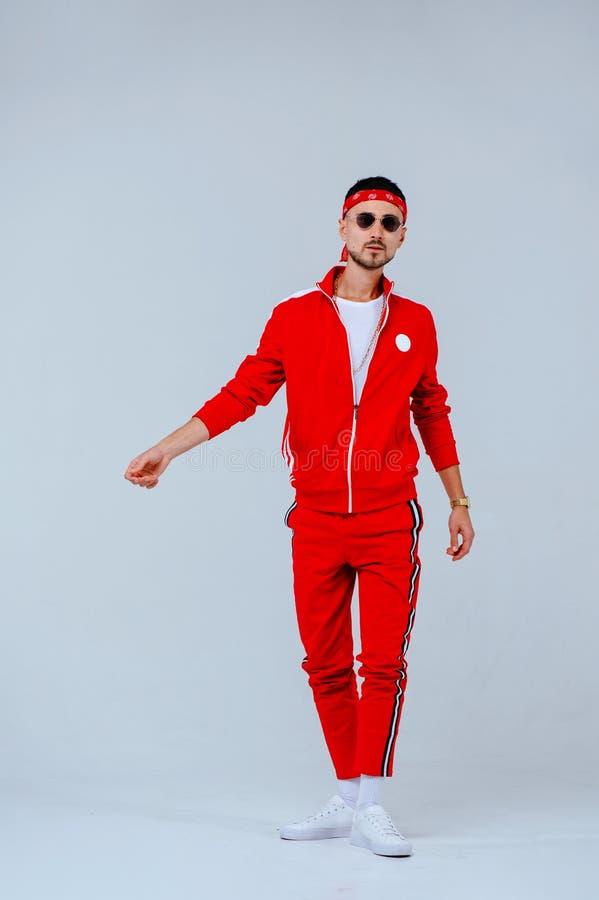 Hälsa gyckel, folksportbegrepp - lycklig ung man som bär den röda sportdräkten på vit bakgrund arkivbild