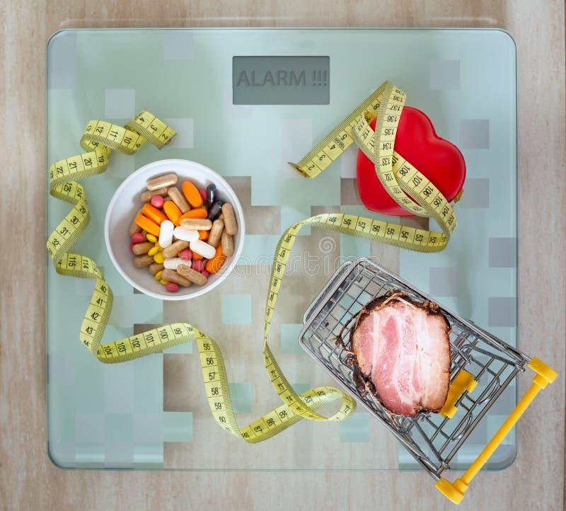 hälsa minnestavlor hjärta samman med fettig mat som ett begrepp av överviktig fattig näring eller ett incitament till en sund lif arkivfoto