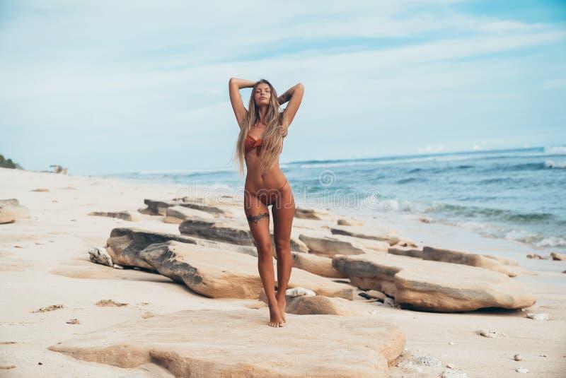 Hälsa skönhet, begrepp för sommarsemester En härlig spenslig modell står på en sandsten vid havet, lyfter hans händer till royaltyfri foto