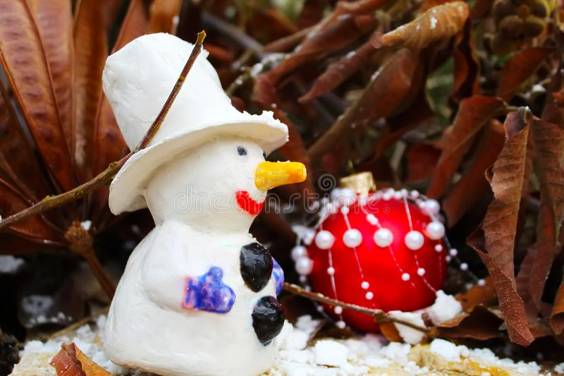 Hälsningkort för glad jul eller för lyckligt nytt år Snögubbe- och julboll arkivfoton