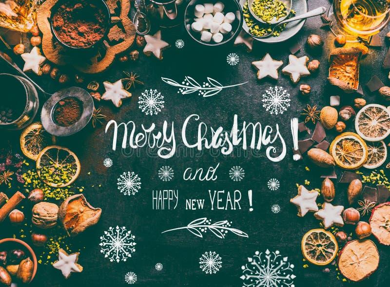 Hälsningkort för glad jul med textbokstäver, kryddor, choklad och kakor på mörk bakgrund med söta matingredienser royaltyfria bilder