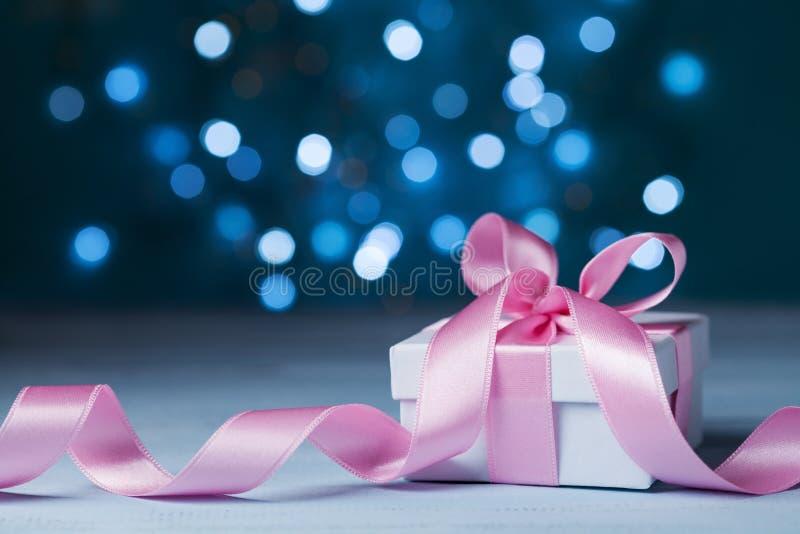 Hälsningkort för jul, nytt år eller bröllop Den vit gåvaasken eller gåva med rosa färger bugar bandet mot magisk bokehbakgrund arkivbild