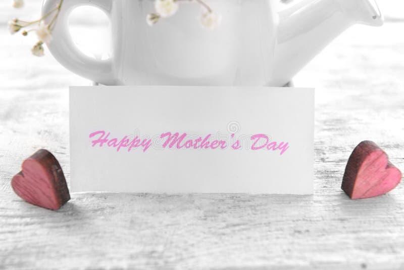Hälsningkort för mors dag med den bevattna krukan på trätabellen, closeup arkivfoto