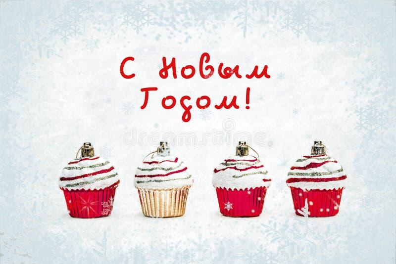 Hälsningkort för nytt år - julstruntsakmuffin på vit snö med snöflingabakgrund Rysk översättning: Lyckligt nytt år arkivbilder