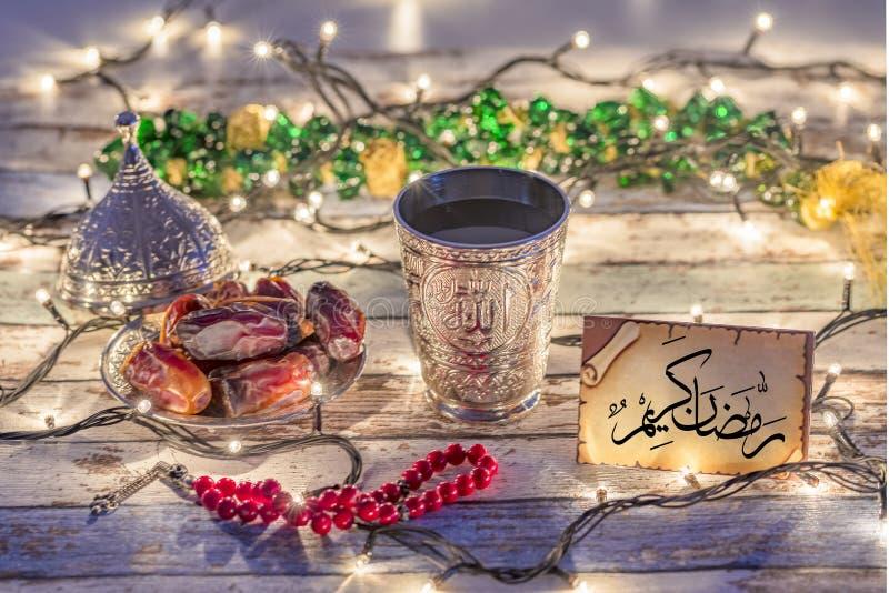 Hälsningkort med arabisk text 'Ramadan Kareem 'med data, radbandet och vattenkoppen arkivfoton