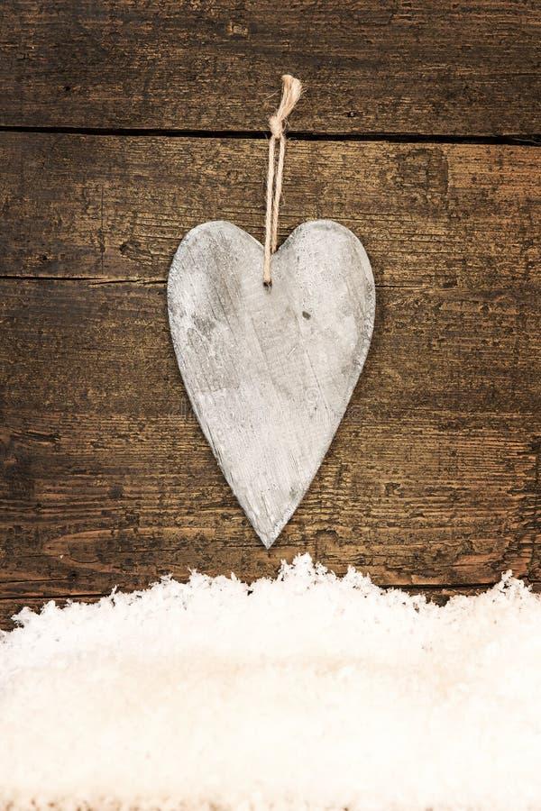Hälsningkort med en trähjärta och snöflingor royaltyfri fotografi