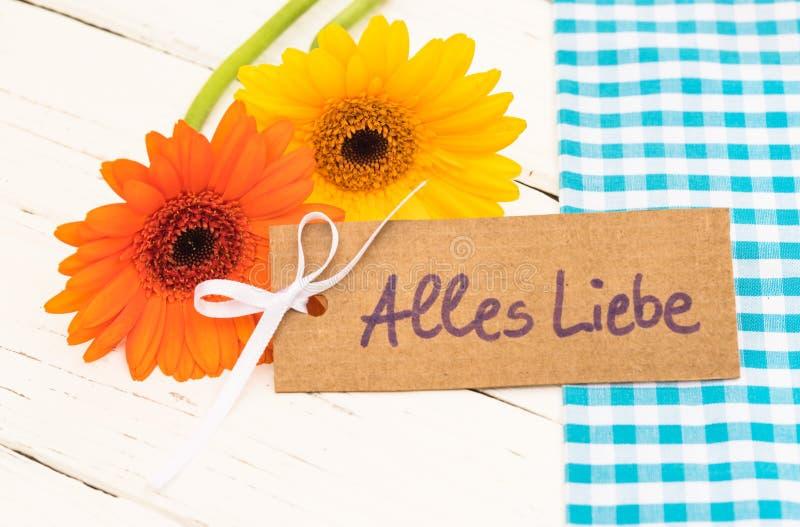 Hälsningkort med tysk text, Alles Liebe, hjälpmedelförälskelse och härliga blommor fotografering för bildbyråer