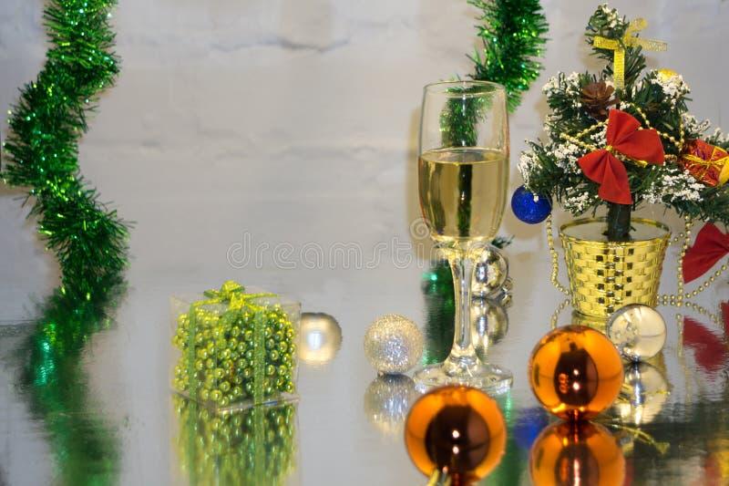 Hälsningkort som göras av jul och bollar för idegransträårsgarnering, glitter, stearinljus och två exponeringsglas av champagne m arkivbild