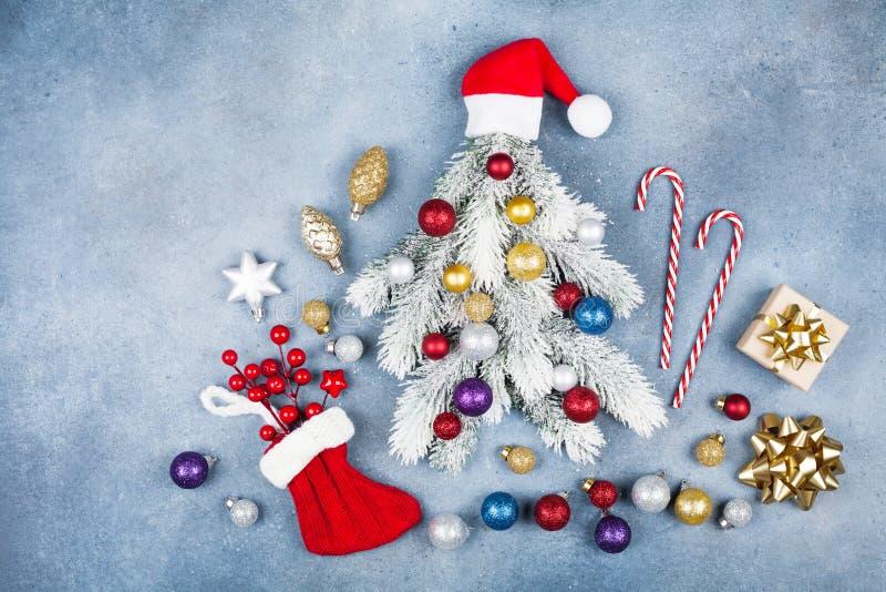 Hälsningkortet med det idérika julgranträdet dekorerade jultomtenhattar, gåvaasken och färgrika bollar på bästa sikt för blå bakg arkivbild