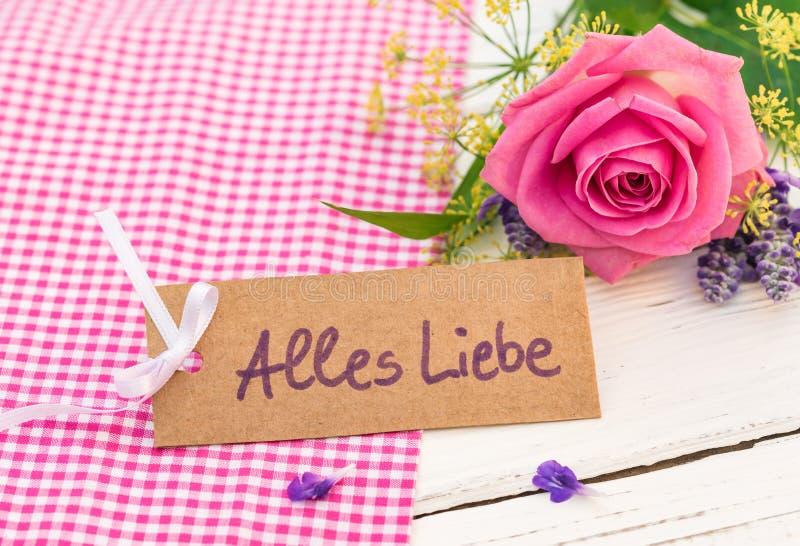 Hälsningkortet med tysk text, Alles Liebe, hjälpmedel älskar och rosa färgrosen för valentin- eller moderdag arkivfoton