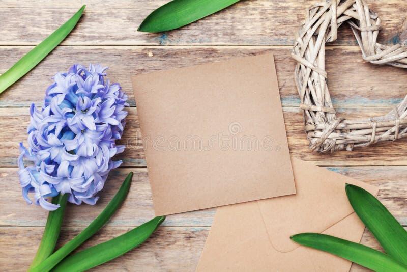 Hälsningkortet på moderdag med det kraft kuvertet dekorerade hyacintblommor och hjärta på lantlig bakgrund Top beskådar