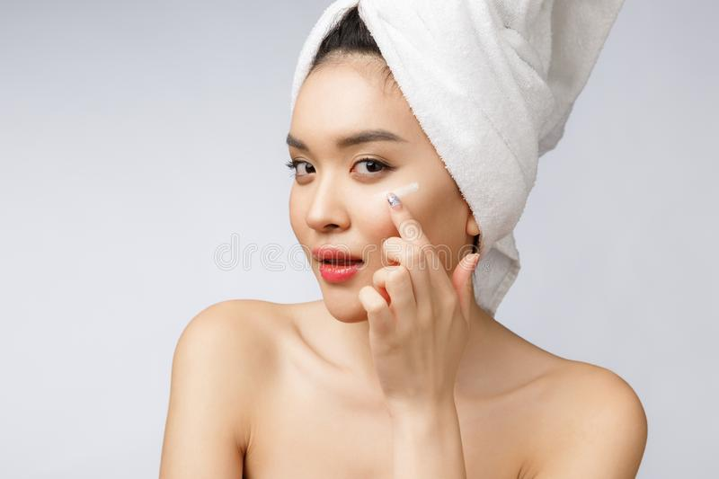 Hälso- och skönhetbegrepp - attraktiv asiatisk kvinna som applicerar kräm på hennes hud, på vit royaltyfri fotografi