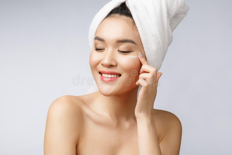 Hälso- och skönhetbegrepp - attraktiv asiatisk kvinna som applicerar kräm på hennes hud, på vit royaltyfria foton