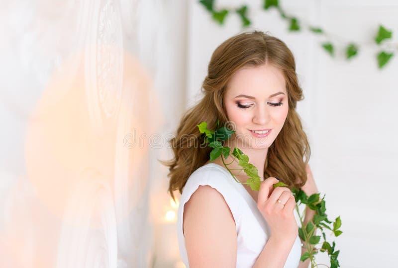 Hälso- och skönhetbegrepp - ung proper kvinnastående som shyly ler, tjockt naturligt hår som försiktigt faller från hennes skuldr royaltyfri fotografi