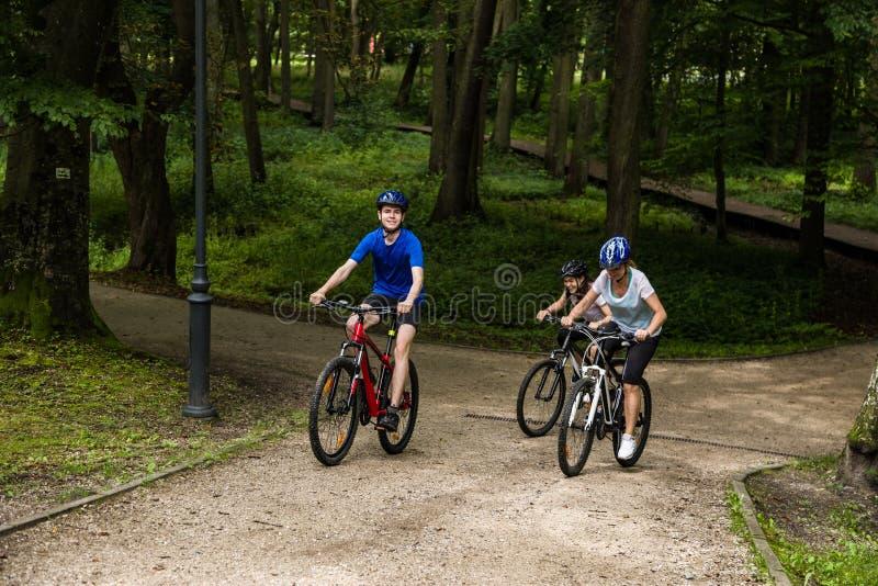 Hälsosam livsstil - lyckliga människor som cyklar i stadsparken royaltyfria foton