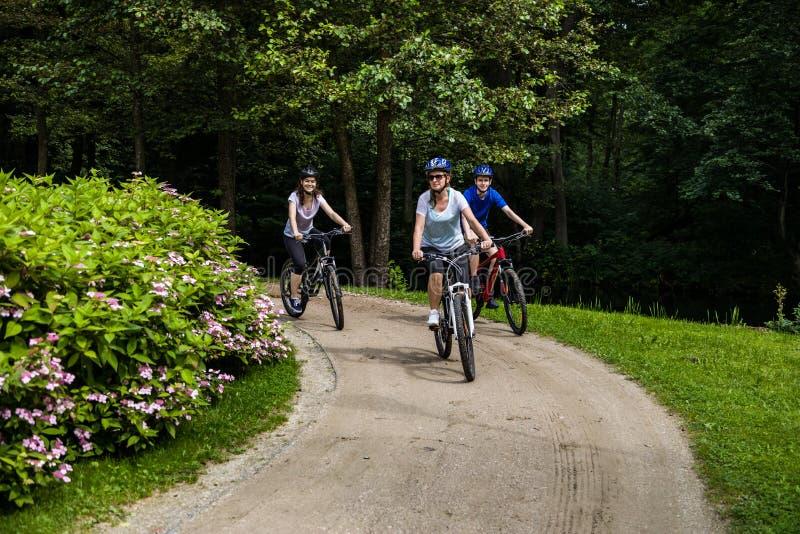 Hälsosam livsstil - lyckliga människor som cyklar i stadsparken fotografering för bildbyråer