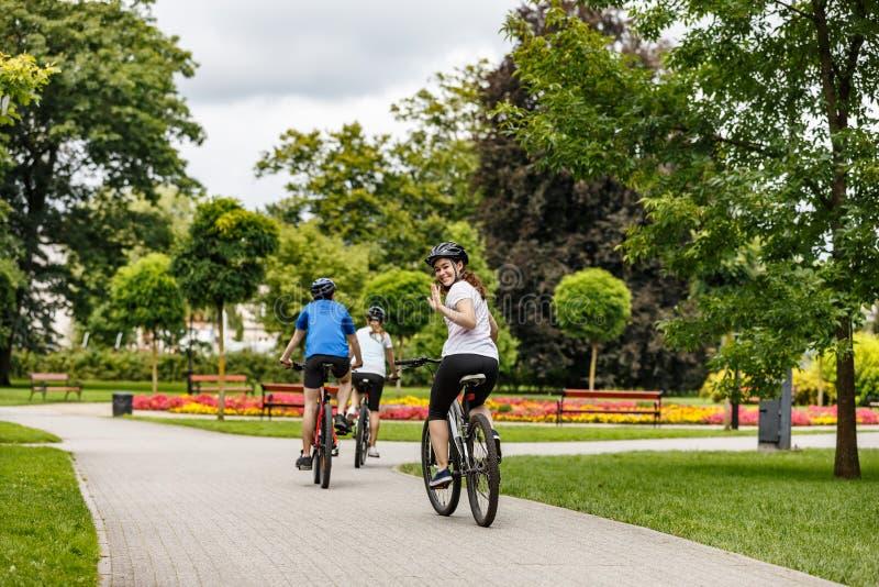 Hälsosam livsstil - lyckliga människor som cyklar i stadsparken royaltyfri bild