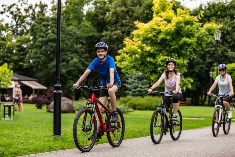 Hälsosam livsstil - lyckliga människor som cyklar i stadsparken arkivbild