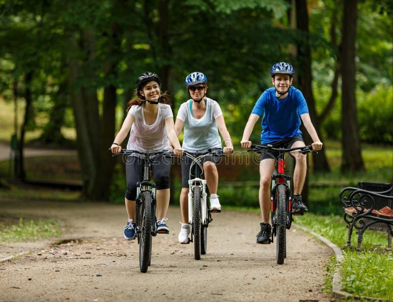 Hälsosam livsstil - lyckliga människor som cyklar i stadsparken arkivfoto