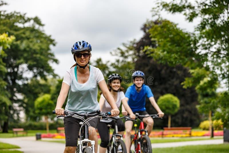 Hälsosam livsstil - lyckliga människor som cyklar i stadsparken royaltyfria bilder
