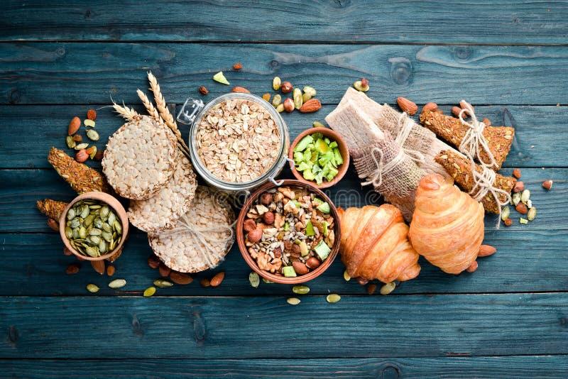 Hälsosamma snacks Stång av havremjöl, kroissant, russin, nötter På blå bakgrund Överkant arkivfoton