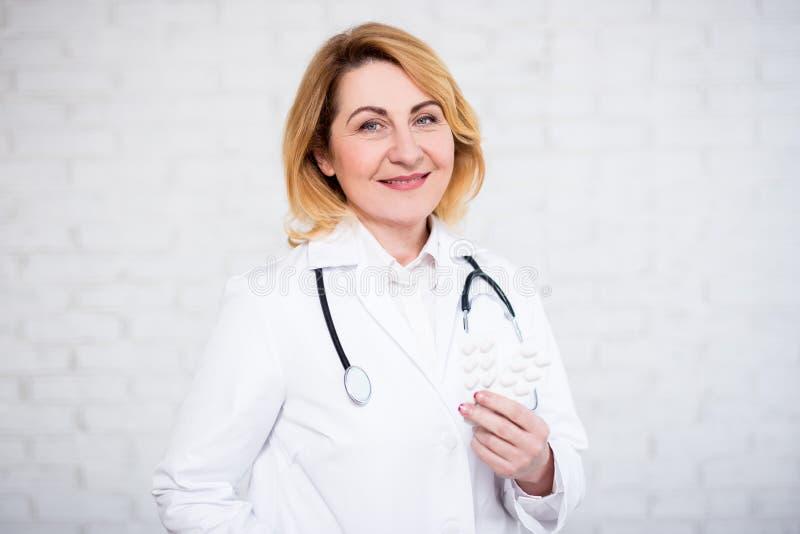Hälsovård- och apotekbegrepp - mogen kvinnlig doktor eller sjuksköterska som rymmer piller över den vita väggen royaltyfri bild