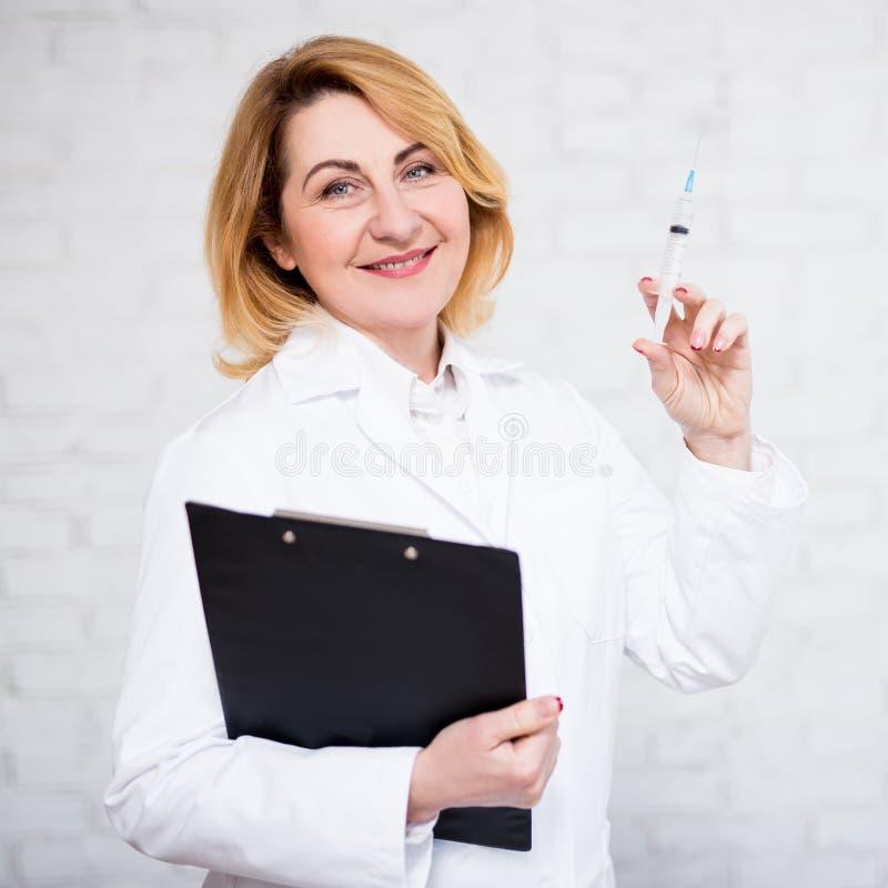 Hälsovård-, vaccinering- och cosmetologybegrepp - mogen kvinnlig doktor eller sjuksköterska med injektionssprutan över den vita v royaltyfri fotografi