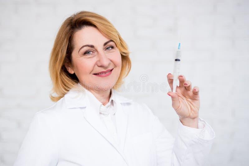 Hälsovård-, vaccinering- och cosmetologybegrepp - mogen kvinnlig doktor eller sjuksköterskainnehavinjektionsspruta över den vita  arkivbild