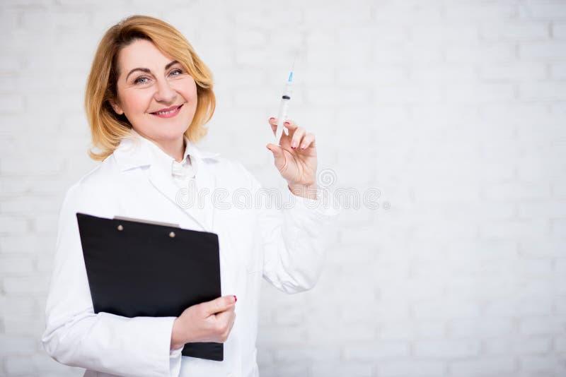 Hälsovård-, vaccinering- och cosmetologybegrepp - mogen kvinnlig doktor som rymmer injektionssprutan och skrivplattan över den vi arkivbild