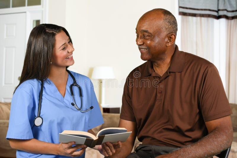Hälsovårdarbetar- och åldringpatientläsebok royaltyfria bilder
