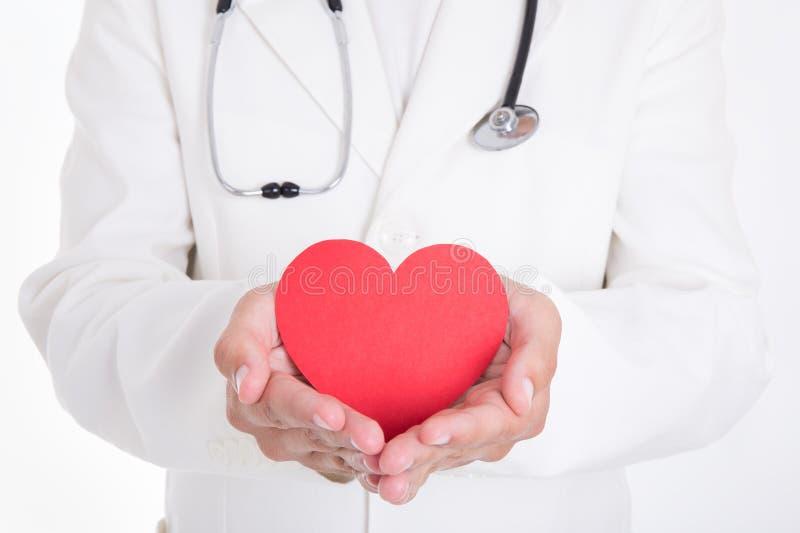 Hälsovårdbegrepp - doktor som rymmer röd hjärta isolerad på vit arkivbild
