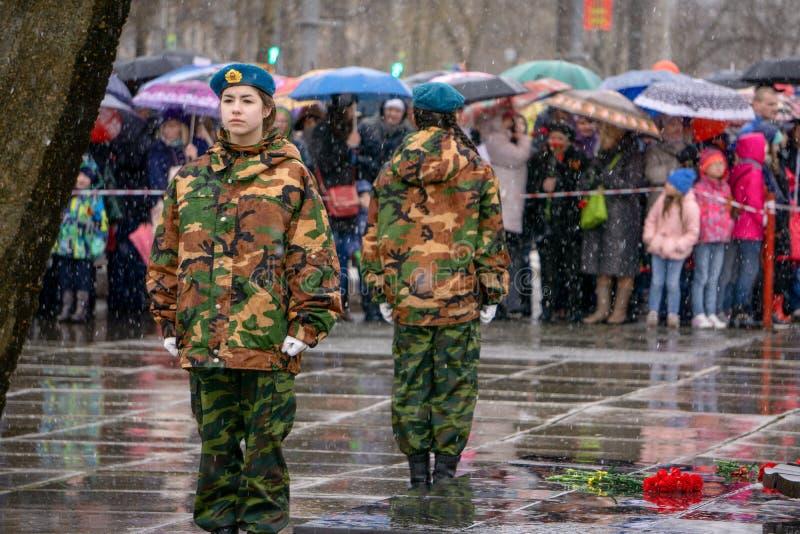 Hält ein Porträt seines Vaters, während er am unsterblichen Regimentmarsch während der Victory Day-Feiern in- Berezniki teilnimmt lizenzfreies stockfoto