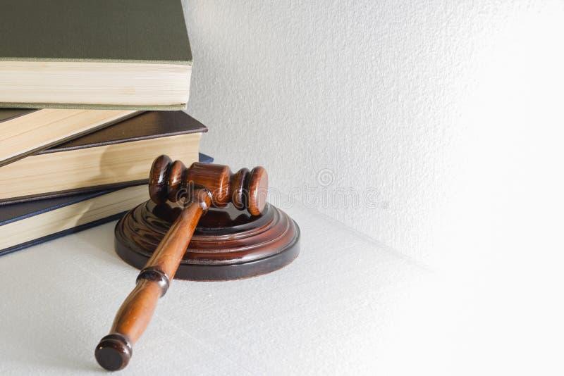 Hämmern Sie Richter auf dem Hintergrund eines Stapels der Bücher, das Bild auf einem hellen Hintergrund stockbilder