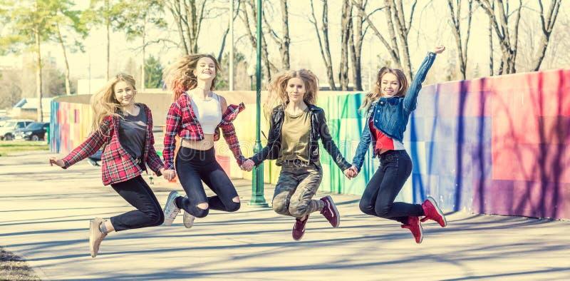 Händchenhalten der jungen Mädchen und zusammen springen stockbild