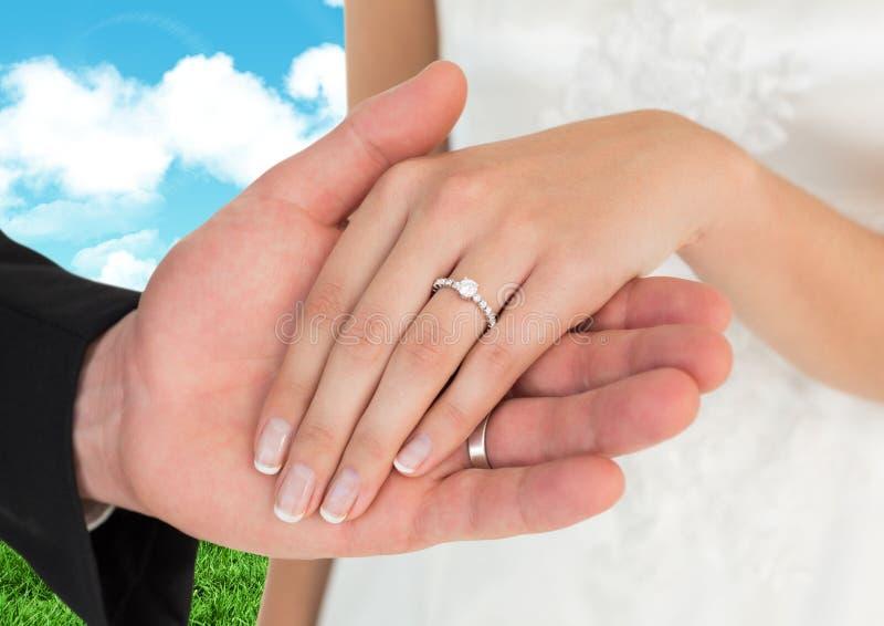 Händchenhalten des verheirateten Paars gegen Himmel im Hintergrund lizenzfreie stockbilder